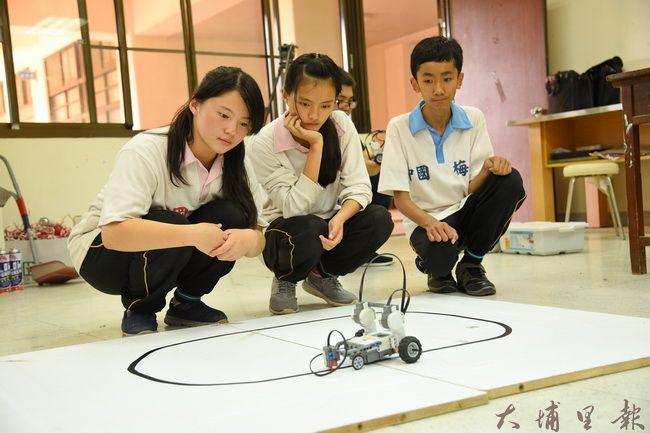 北梅國中參賽團隊設計機器人自走車持重物行走,規定時間內走最多圈便能奪下第一。(廖仲政攝)