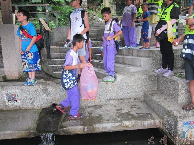 活動中最重要一環,每到一個定點,溪南國小孩子們就會拿起手中垃圾袋,把它裝滿,孩子所到之處,垃圾不落地。(金城嚴 攝)
