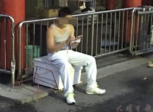 一名在鐵山里廣興紙寮、西鎮堂出沒的男子為了抓寶可夢,竟然未察覺屁股上坐的是蜂箱。(羅維振攝)