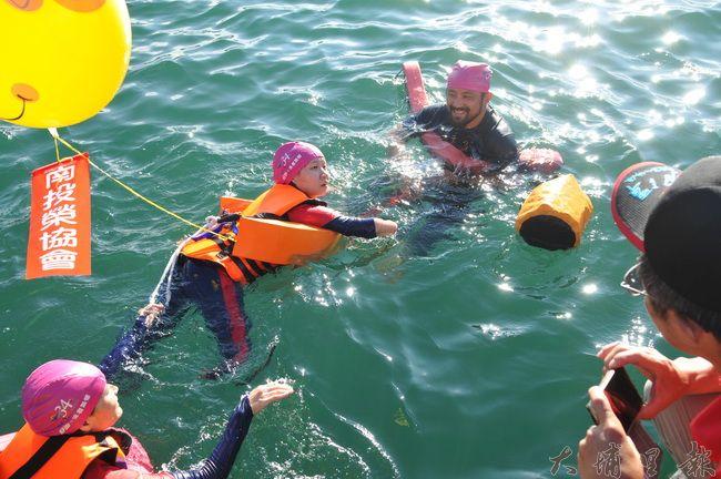 2016日月潭萬人泳渡,生命鬥士郭韋齊在教練(前)及母親(後)的守護下,奮力滑動沒有手掌、腳掌的四肢往前進。(柏原祥攝)