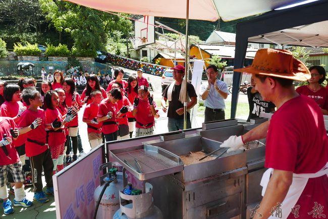 小吃店老闆至合作國小義煮,學生鼓掌歡迎豪大大雞排志工們。