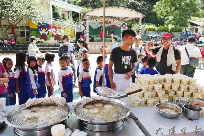 小吃店老闆至合作國小義煮,學童來到橋頭邊肉圓攤位準備領取美食。