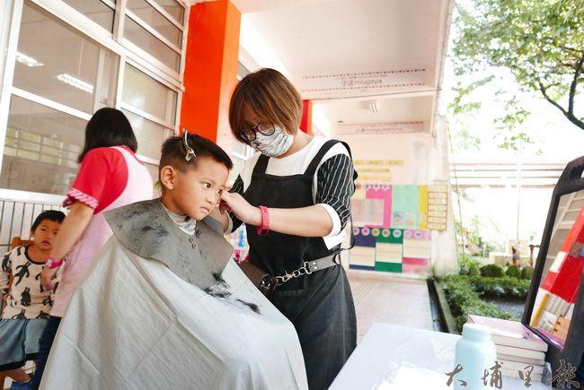 小吃店老闆至合作國小義煮,歐格髮型造型師為學童義剪。