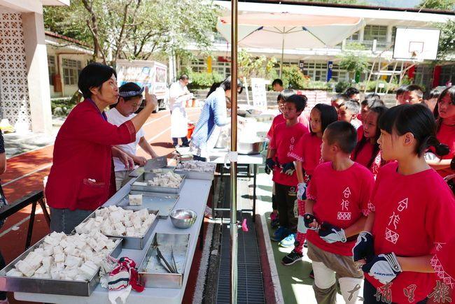 小吃店老闆至合作國小義煮,.全一珍蘿蘿蔔糕志工阿姨為學童解說蘿蔔糕製作過程。