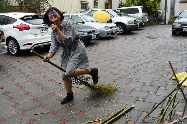 籃城書房店長,騎著剛做好的竹掃把,送完包裹回來,有如動畫《魔女宅急便》女主角。(金城嚴 攝)