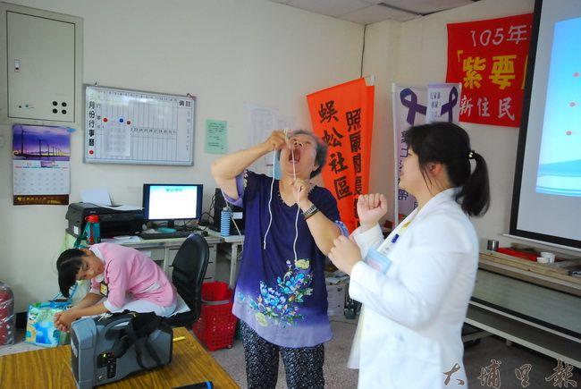 護理師許智淳教導長輩使用牙線,阿嬤急著示範,忘記手上拿的是繩子。(金城嚴 攝)