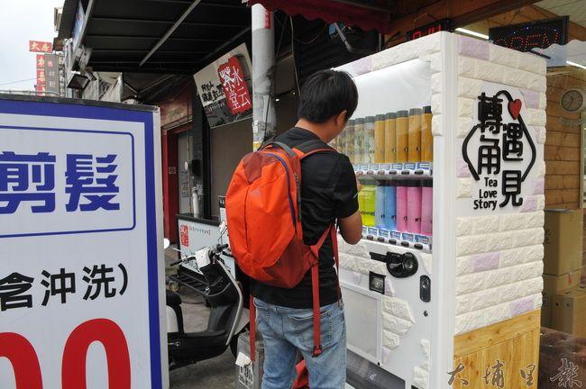 埔里鎮鬧區出現一座以整株玫瑰花入瓶的「手搖飲料」自動販賣機,吸引好奇消費者選購。(柏原祥 攝)