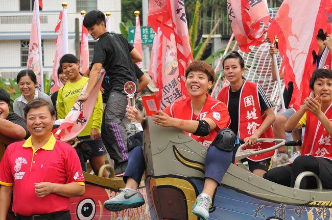 台灣體大「龍成女戰隊」再度稱霸國姓搶成功戰船競速比賽,隊員坐在戰船上舉起獎盃,相當的興奮。(柏原祥 攝)