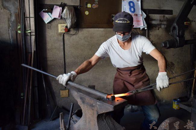 埔里打鐵街守護傳統工藝,圖為「金利興」頭家彭田處理火紅的金屬條。(洪阿仙 攝)