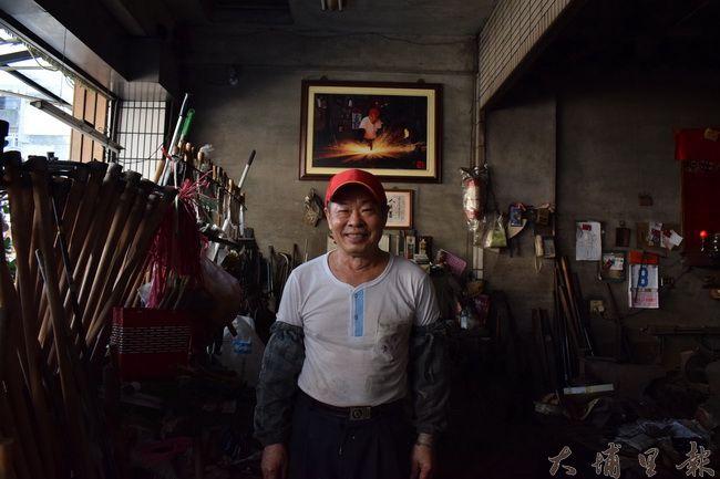 埔里打鐵街維繫傳統工藝,圖為「金合源」頭家彭進富,後方是攝影師贈送的打鐵影像。(洪阿仙 攝)