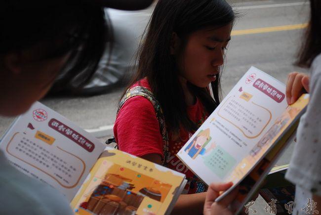 同學認真看著遊戲書,想解出書內的任務。(金城嚴 攝)
