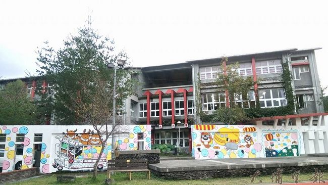 仁愛國中新彩繪圍牆與背後的原民風味的校舍形成了強烈的對比。