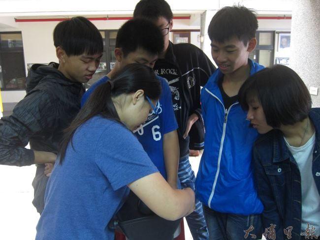 社區青少年們看著社工員操作機器,以利待會順利運作。(照片提供 良顯堂基金會)