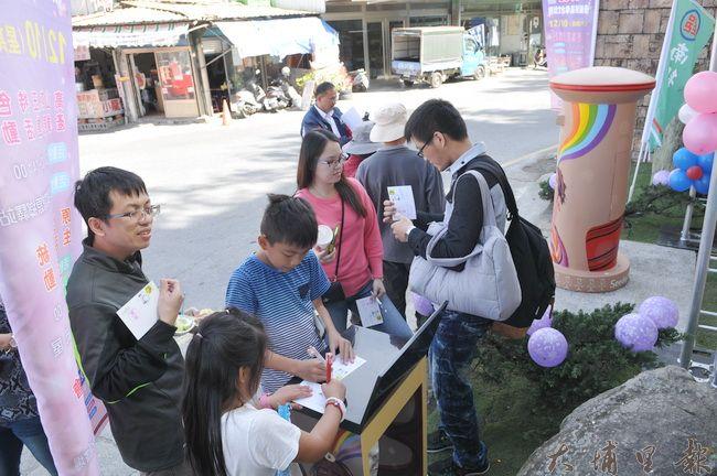 賽德克族文化特色郵筒5日在仁愛鄉公所前揭幕,許多遊客前來蓋紀念章。(柏原祥 攝)