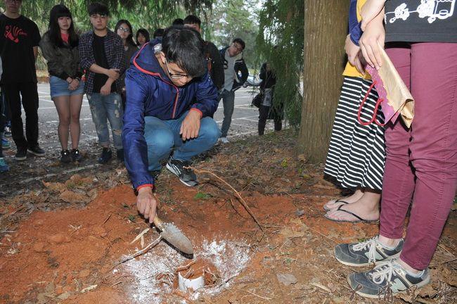 暨大校犬「喬妹」日前車禍過世,遺體火化後,暨大同學輪流覆土,將牠安葬在校園內,並舉行追思儀式。(柏原祥 攝)
