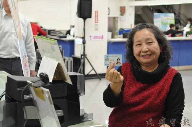 健保署在埔里鎮公所設置製卡、愛心轉運站,羅姓婦人搶得頭香,補辦埔里第一張健保卡。(柏原祥 攝)
