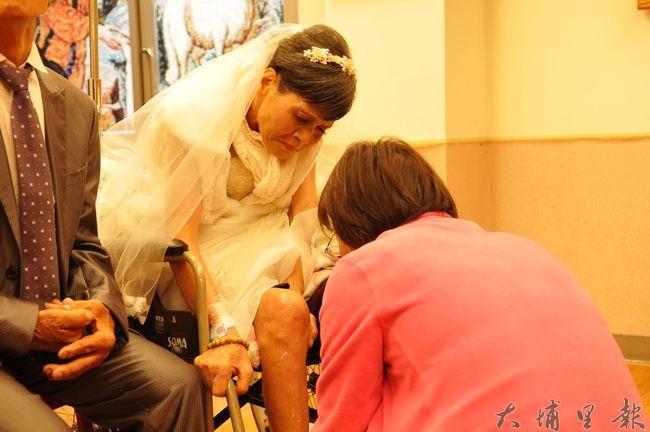 在埔基醫院小教堂拍攝婚紗過程中,林富美阿嬤腿部因癌細胞轉移突劇烈疼痛,護理人員急忙為她按摩止痛。(柏原祥 攝)