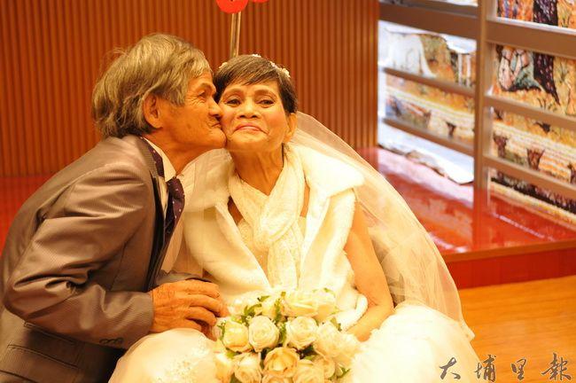 在埔基醫院拍攝婚紗過程中,陳木貴阿公在林富美阿嬤臉上獻吻。(柏原祥 攝)