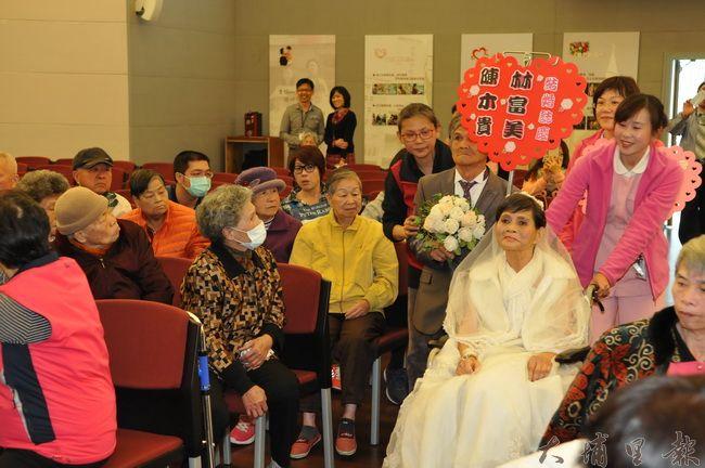 醫護人員協助下,林富美阿嬤坐著輪椅進入婚禮的禮堂。(柏原祥 攝)