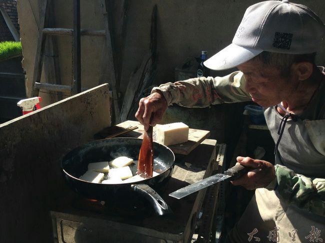 大阿伯親手煎著濃濃蘿蔔味的蘿蔔糕請大家吃。(穀笠合作社提供)