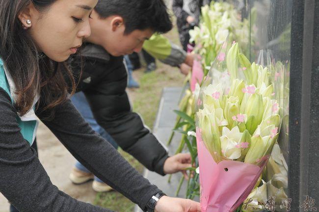 海外228遺屬返鄉團至埔里烏牛欄戰役紀念碑憑弔,民眾獻上百合花追思。(柏原祥 攝)
