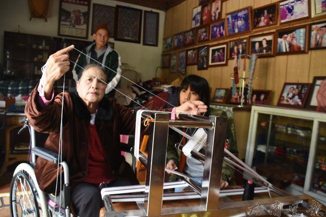 國寶張胡愛妹(張媽媽)雖然盆骨受傷稍有不便,仍細心教導孩子傳承織布技術。(金城嚴 攝)