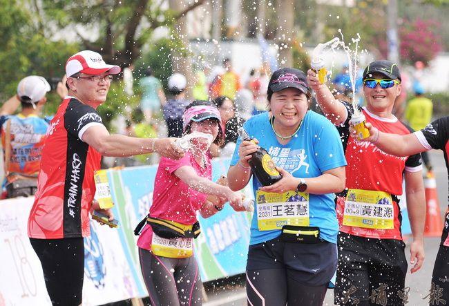 埔里山城派對馬拉松完賽,王姓跑者進到終點門,好友狂噴啤酒為她完成初馬慶賀。(柏原祥 攝)