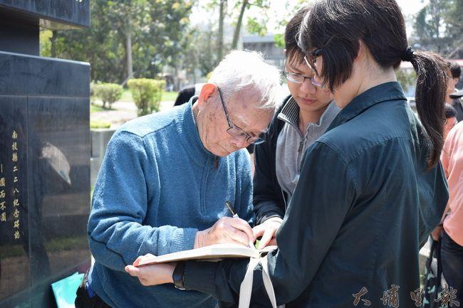 烏牛欄戰役講談結束後,「二七部隊」警備隊長黃金島為讀者新書簽名。(洪健鈞 攝)