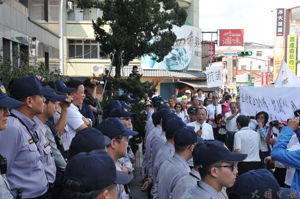數百位反對鎮公所在第七公墓(鯉魚潭公墓)興建殯儀館的鎮民要求鎮長周義雄出面,周義雄(左側抱胸微笑者)出面回應。(柏原祥 攝)