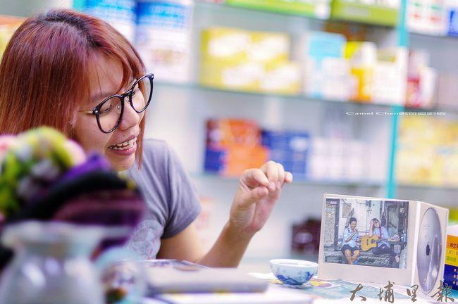 曾立馨進駐埔里,要為社區創作自己的歌,圖為她在新仁壽藥局說明自身的創作。(柏原祥 攝)