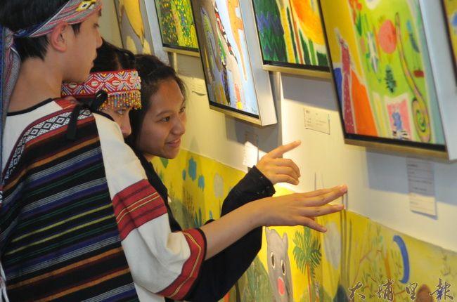 仁愛國中同學們參與《蝸牛與天使》畫展開幕,仔細端詳作品。(柏原祥 攝)