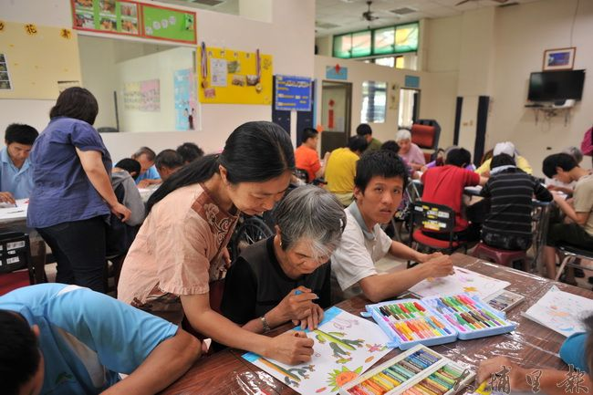 炫寬愛心教養家園藝術治療老師楊繐鳳指導園民藝術創作的過程。(柏原祥 攝)