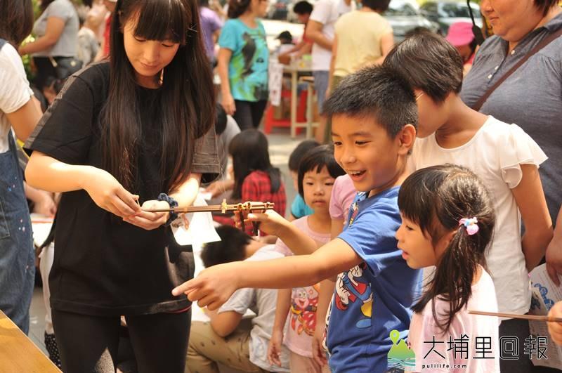 埔里在地文學、書畫家王灝生前經常帶領孩童製作童玩,埔里圖書館舉辦童玩體驗活動紀念他,圖為小朋友開心玩竹筷橡皮筋槍。(柏原祥 攝)