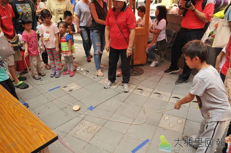 埔里在地文學、書畫家王灝生前經常帶領孩童製作童玩,埔里圖書館舉辦童玩體驗活動紀念他,圖為小朋友開心玩博狀元餅。(柏原祥 攝)