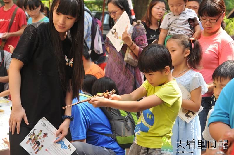 埔里在地文學、書畫家王灝生前經常帶領孩童製作童玩,埔里圖書館舉辦童玩體驗活動紀念他,圖為小朋友玩竹筷槍。(柏原祥 攝)