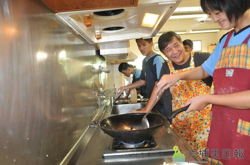 埔里國中特教班學生由王子華指導廚藝,聞到自己親手炒菜的香氣,特教生露出開心的笑容。(柏原祥 攝)