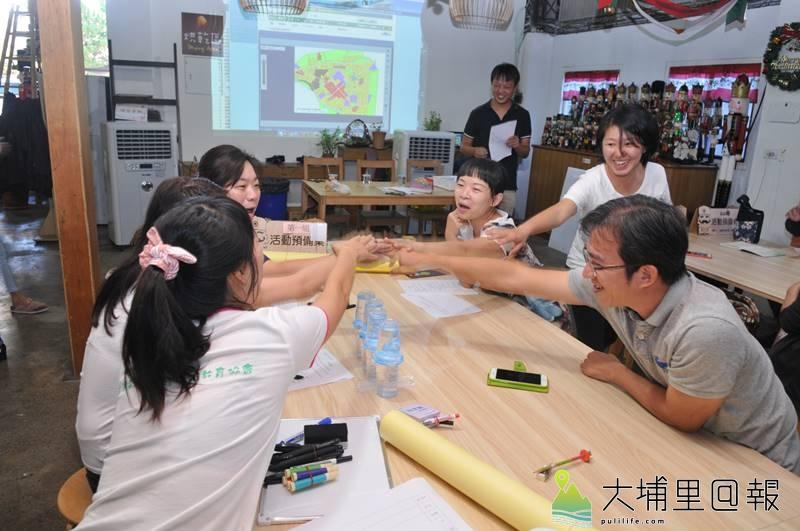 埔里鎮一群家長舉辦兒童公園圓夢工坊,分組會議中,組員擊掌凝聚共識。(柏原祥 攝)