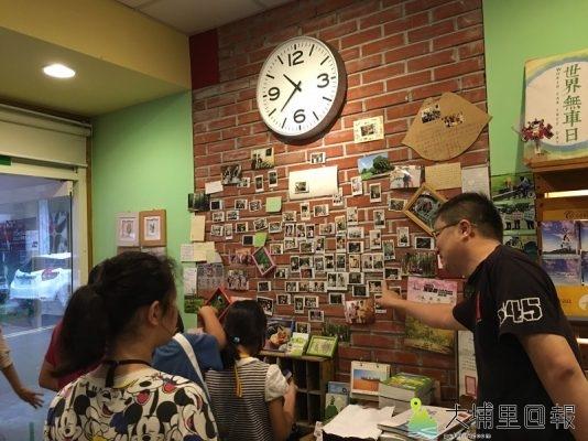 【圖說】店長親切地為小小記者們解說牆上的照片,以及店內的印章。(圖/邱品蓉拍攝)