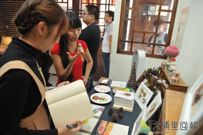 暨南國際大學在永樂園青年旅館成立R立方學堂,提供青年工作空間,圖為設計師洪湘紜(紅衣者)向來賓說明自己設計的插畫手工書。(柏原祥 攝)