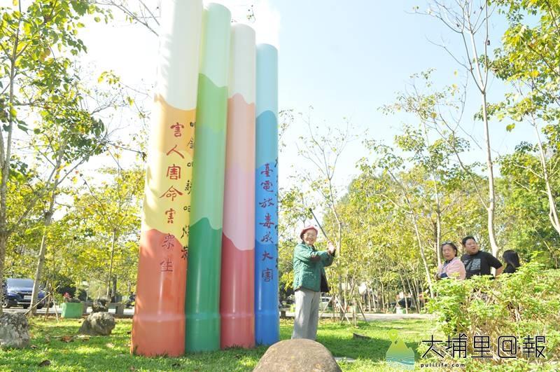 埔里鎮牛耳藝術渡假村創立30週年,黃炳松發表新作品,以柺杖作勢擊打帶來空汙的台中火力發電廠煙囪。(柏原祥 攝)