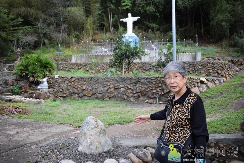 位於「米薩感恩園」,指著「玉山之石」的下山操子。(洪健鈞 攝)