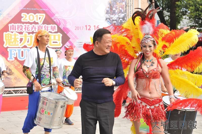 埔里鎮公所將於16日舉辦森巴踩街活動,埔里鎮長周義雄與森巴女郎一同熱舞。(柏原祥 攝)