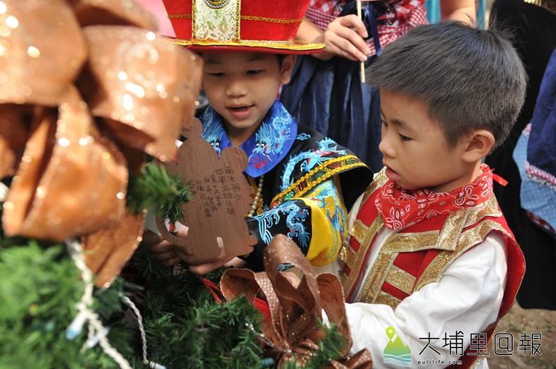 國際聖誕音樂派對在埔里演習林舉辦,穿著多國特色服飾的小朋友在耶誕樹掛上祈福卡。(柏原祥 攝)