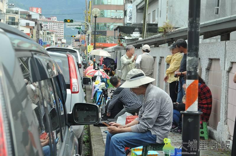 攝影人士為拍攝埔里國中舉辦的銅梁火龍表演,在學校圍牆外人行道以板凳及腳架「卡位」。(柏原祥 攝)