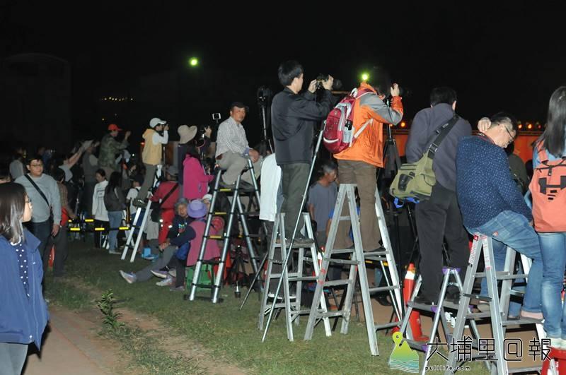 攝影人士為拍攝埔里國中舉辦的銅梁火龍表演,架高梯拍攝,但此舉也影響了後方觀者視線。(柏原祥 攝)