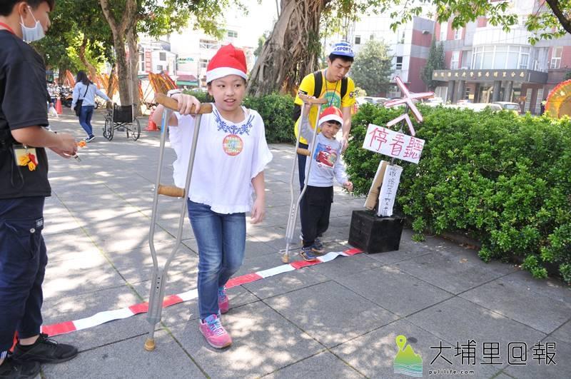埔里無車日活動中,小朋友撐柺杖行走,體會殘障人士的不便。(柏原祥 攝)
