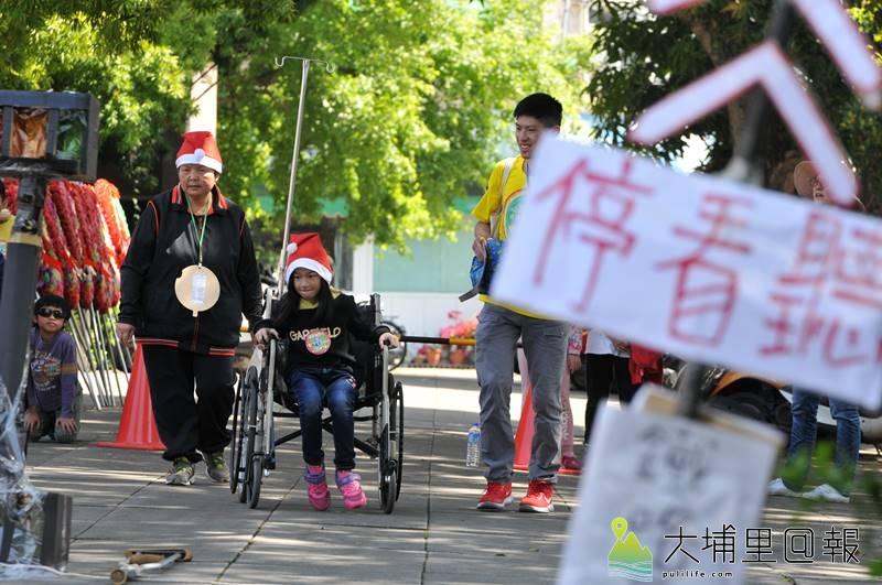 埔里無車日活動中,小朋友坐輪椅過各種交通關卡,體會殘障人士的不便。(柏原祥 攝)