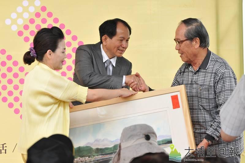 前輩畫家黃義永出席廖志城參選埔里鎮長記者會,推薦廖志城對於埔里藝文活動非常的幫忙,並致贈自身畫作。(柏原祥 攝)