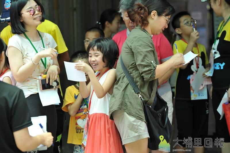 暨大諮人系同學及埔里國小師長舉辦多元文化親子交流活動,在默契大考驗關卡,母女露出會心的微笑。(柏原祥 攝)