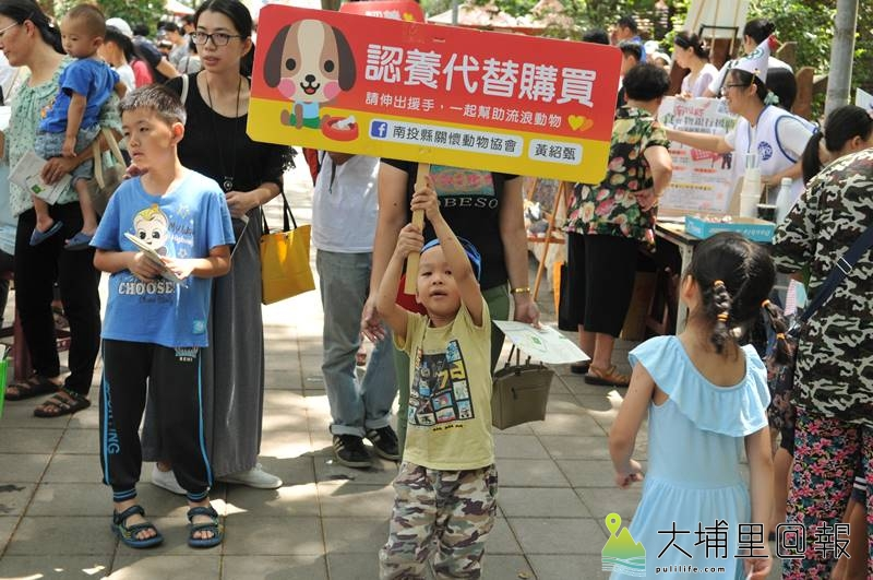 埔里生態城鎮日於啄木鳥步道舉辦,小朋友手持動保立牌,推廣「認養代替購買」,幫助流浪動物。(柏原祥 攝)